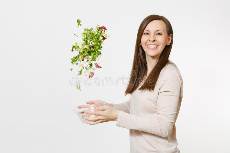 Young happy fun woman standing and throwing up salad from glass bowl isolated on white background. Proper nutrition. Vegetarian food, healthy lifestyle royalty free stock images