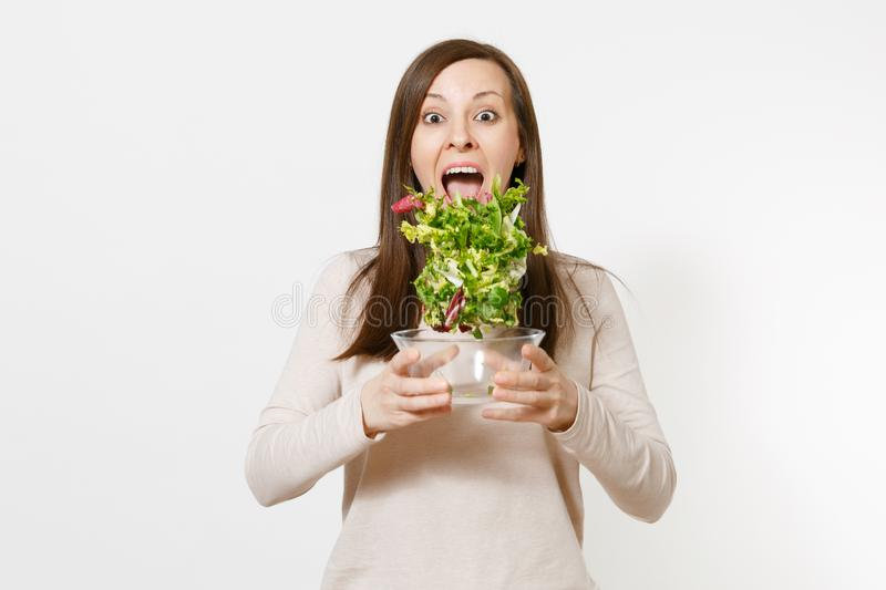 Young happy fun woman standing and throwing up salad from glass bowl isolated on white background. Proper nutrition. Vegetarian food, healthy lifestyle stock image