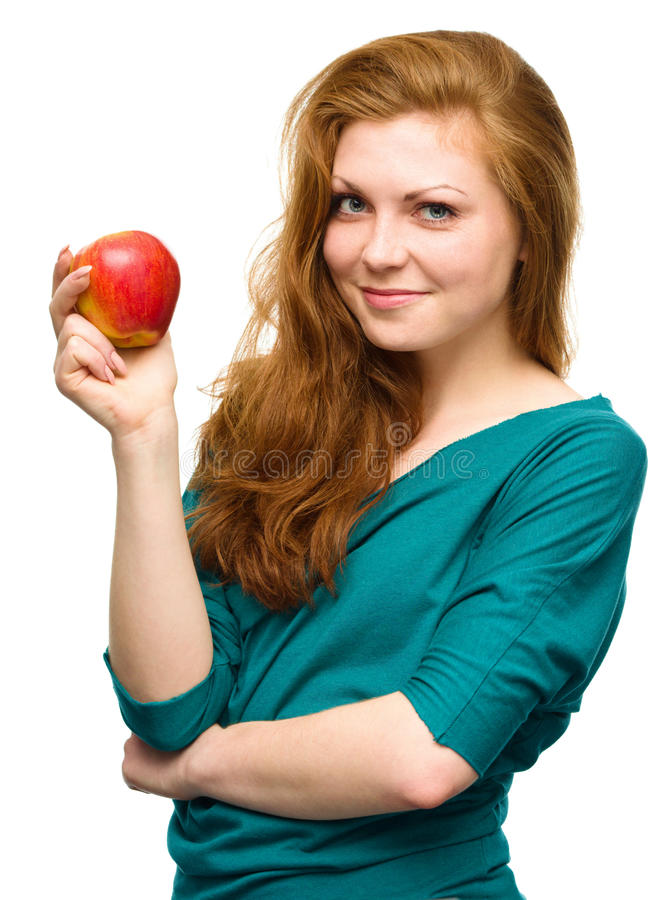 Young happy girl with apple. Young happy girl is holding red apple, isolated over white stock image