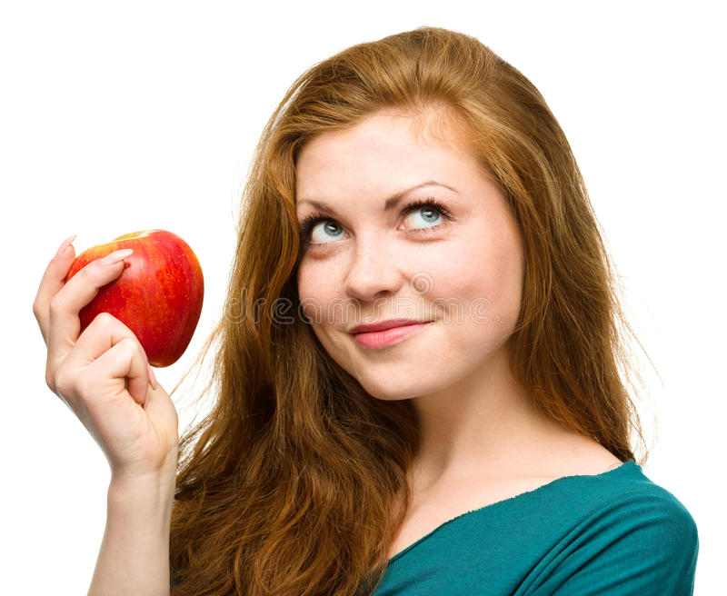 Young happy girl with apple. Young happy girl is holding red apple and looking up, isolated over white stock photos