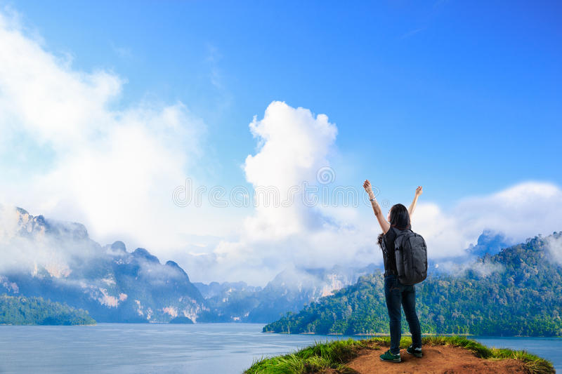 Young happy girl with backpack standing near big river with raised hands royalty free stock image