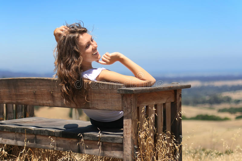 Young happy girl on a bench royalty free stock image