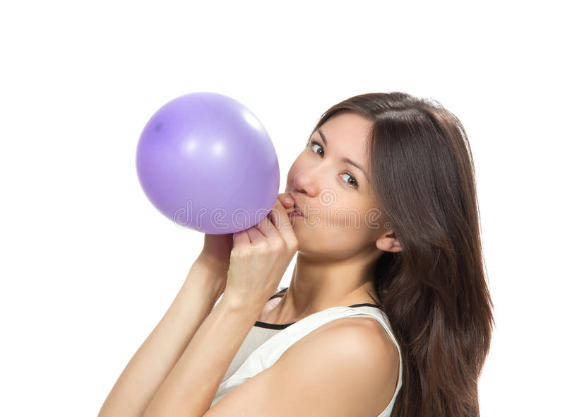 Young happy girl blowing balloon