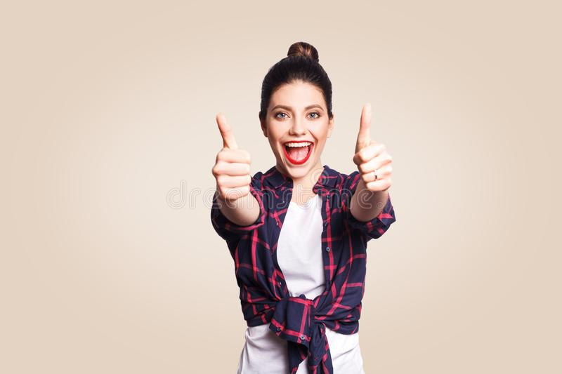 Young happy girl with casual style and bun hair thumbs up her finger, on beige blank wall with copy space looking at camera with t. Oothy smile. focus on face stock photos