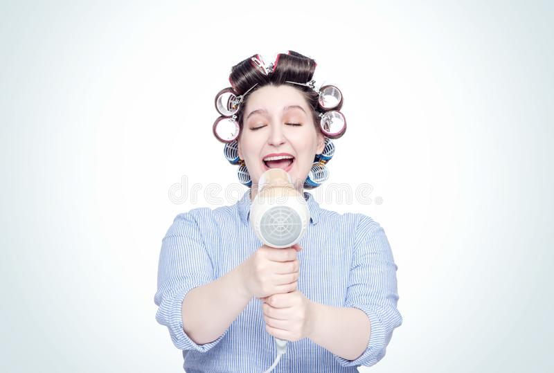 Young happy girl in hair curlers sings into hairdryer like a microphone. Front view. stock images