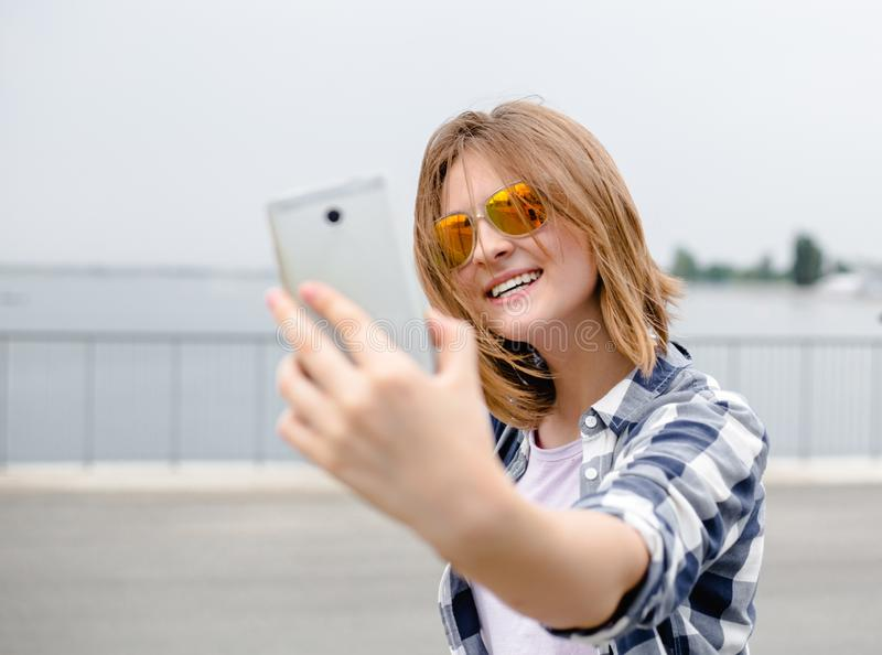 Young happy girl in hipster making selfie on phone.  stock image