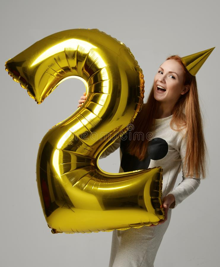 Young happy girl with huge gold digit balloon as a present for birthday party. Smiling on gray background royalty free stock image