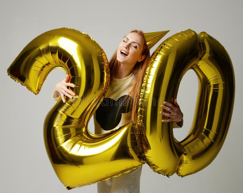 Young happy girl with huge gold digit twenty balloons as a present for birthday. Party on gray background stock image