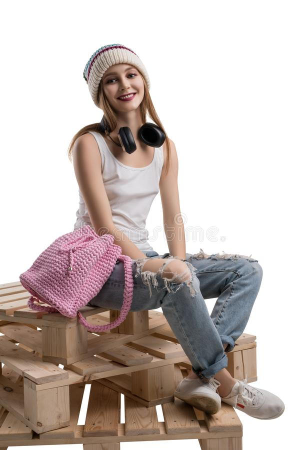 Young happy girl in knitted hat isolated shot. Young happy girl in knitted hat, white t-shirt and torn jeans sitting on wooden pallets isolated shot royalty free stock photo