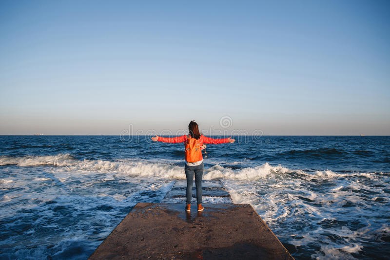 Young happy girl with orange backpack standing on a seaside breathing fresh air raising arms enjoying the view stock images