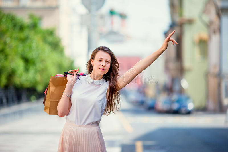Young happy girl with shopping bags catch a taxi. Portrait of a beautiful happy woman standing on the street holding royalty free stock image