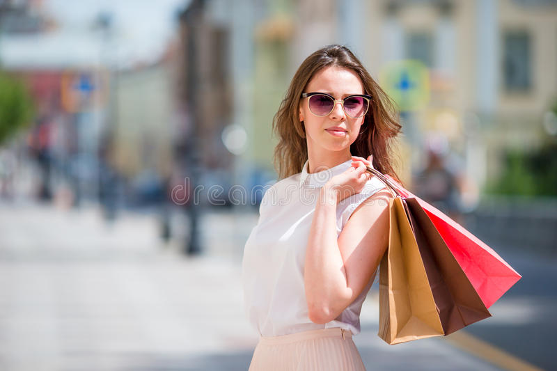 Young happy girl with shopping bags outdoors. Portrait of a beautiful happy woman standing on the street holding stock photos