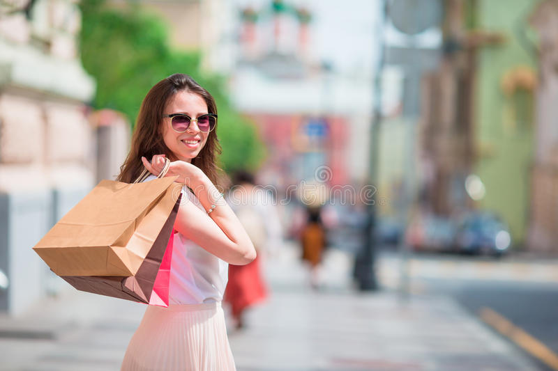 Young happy girl with shopping bags outdoors. Portrait of a beautiful happy woman standing on the street holding royalty free stock photos