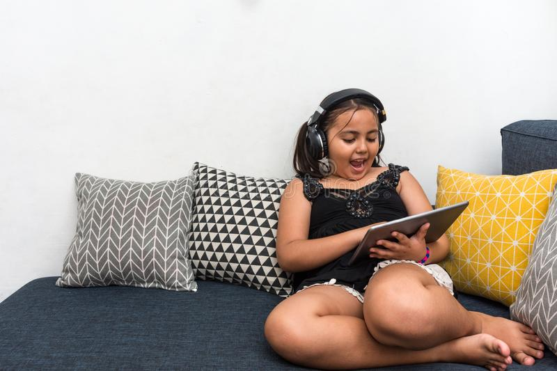 Young happy girl sitting on sofa using tablet listening to music with headphones royalty free stock image