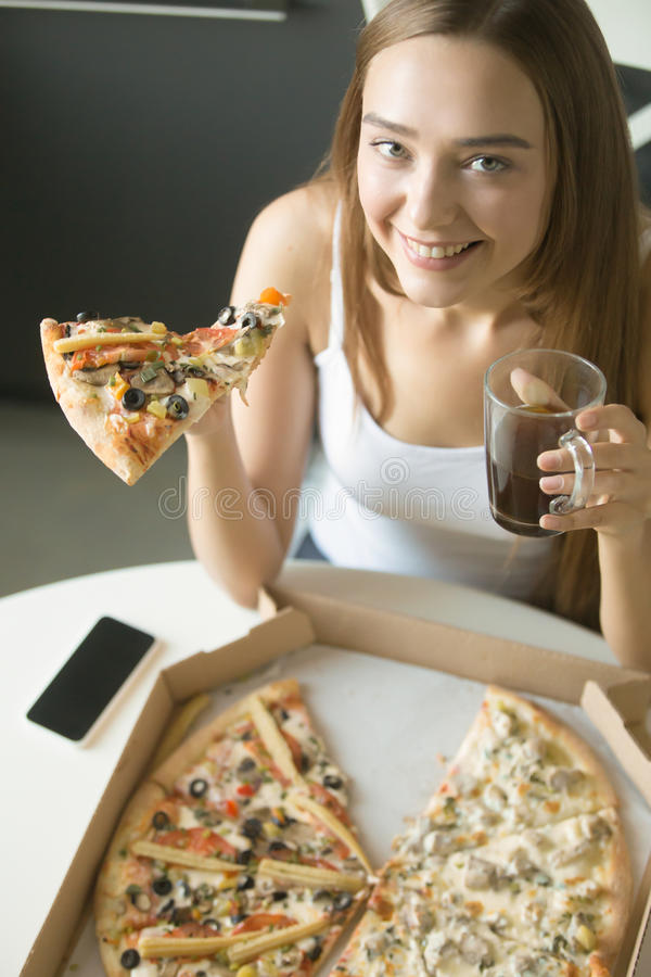 Young happy girl with a slice of pizza. Taken from the open box. Top view, looking at the camera stock images