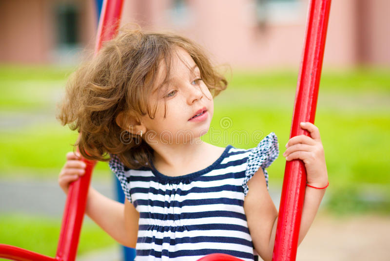 Young happy girl is swinging in playground royalty free stock photography