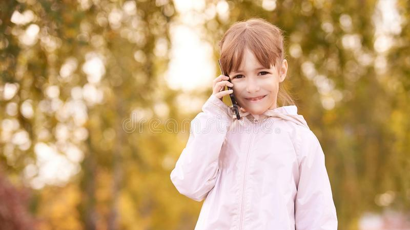 Young happy girl talks cellphone. Phone roaming. People with smartphone. Autumn background royalty free stock image