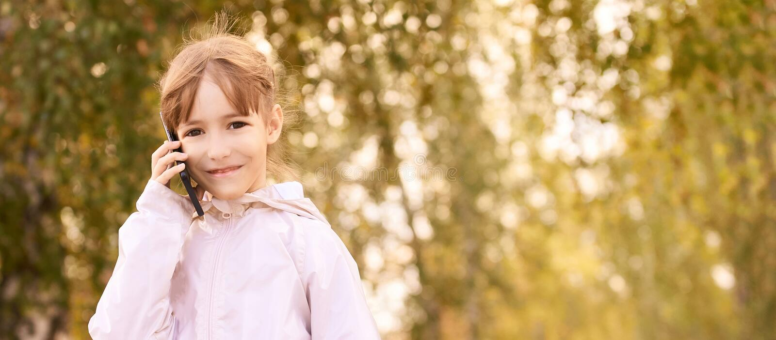 Young happy girl talks cellphone. Phone roaming. People with smartphone. Autumn background.  royalty free stock photo