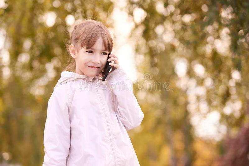 Young happy girl talks cellphone. Phone roaming. People with smartphone. Autumn background stock image