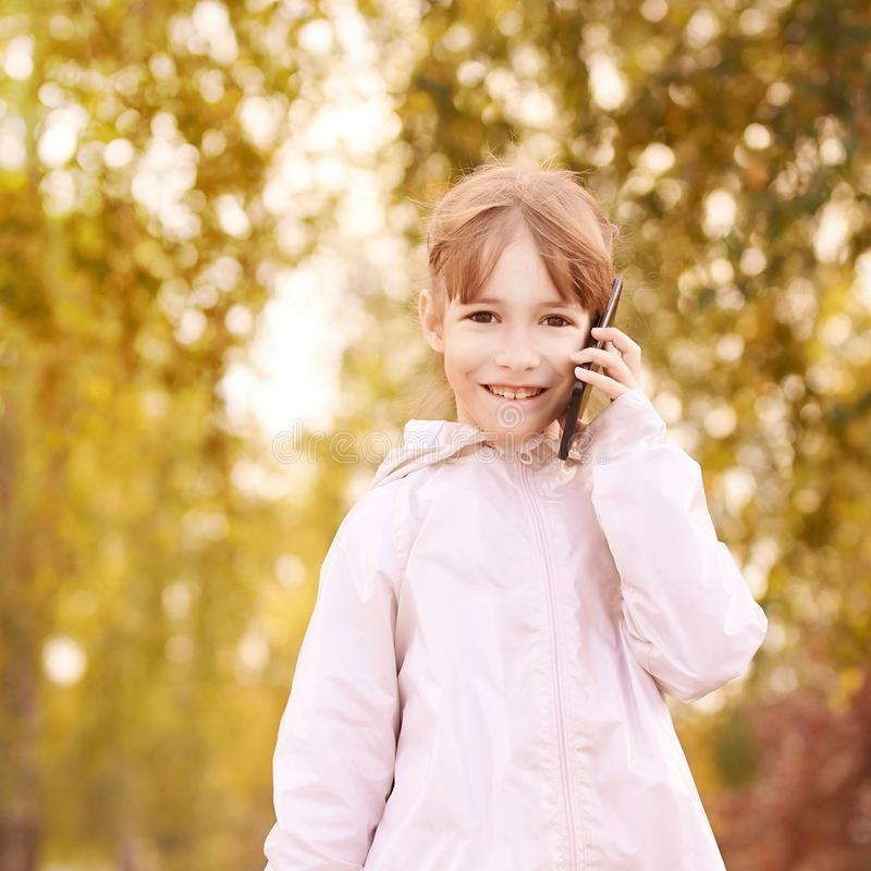 Young happy girl talks cellphone. Phone roaming. People with smartphone. Autumn background.  stock image