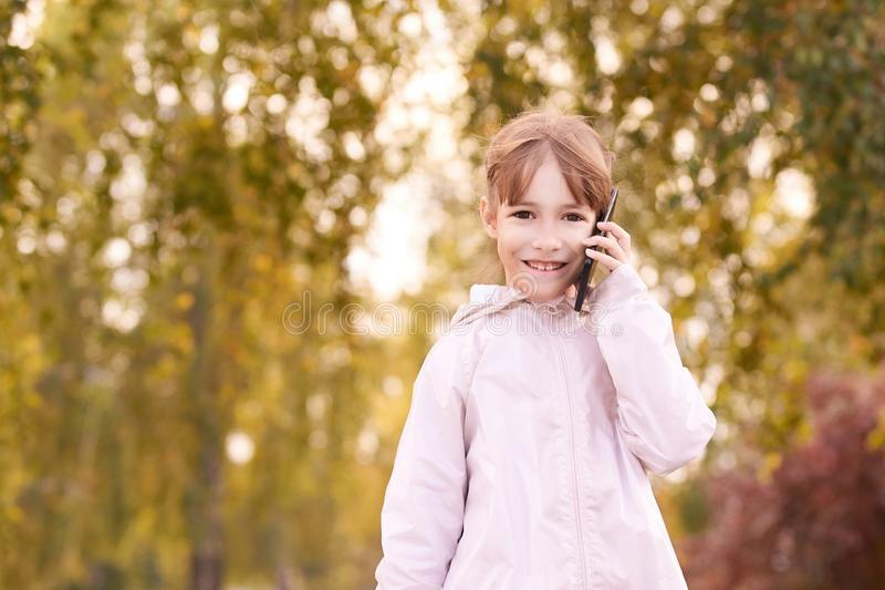 Young happy girl talks cellphone. Phone roaming. People with smartphone. Autumn background.  royalty free stock photos