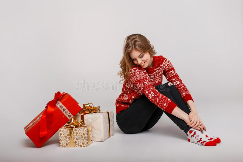 Young happy girl in vintage winter sweater sits near gifts. Young happy girl in vintage winter sweater sits near gifts royalty free stock photography