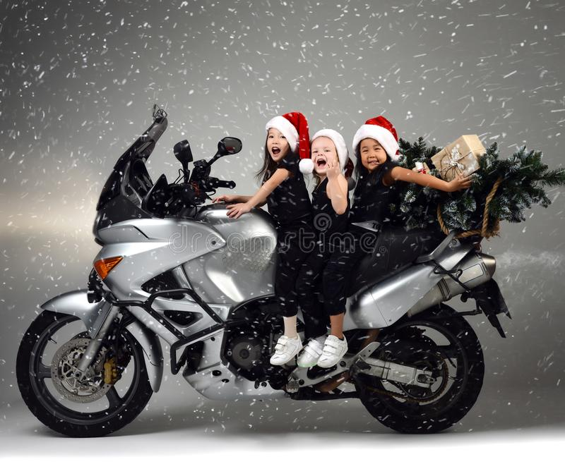 Young happy girls kids ride a motorcycle bike in santa hat and christmas tree stock photography