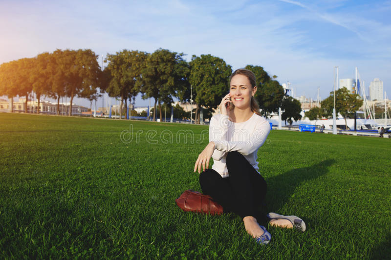 Young happy gorgeous female speaking on mobile phone while sitting on a law in park in beautiful sunny day, stock photos