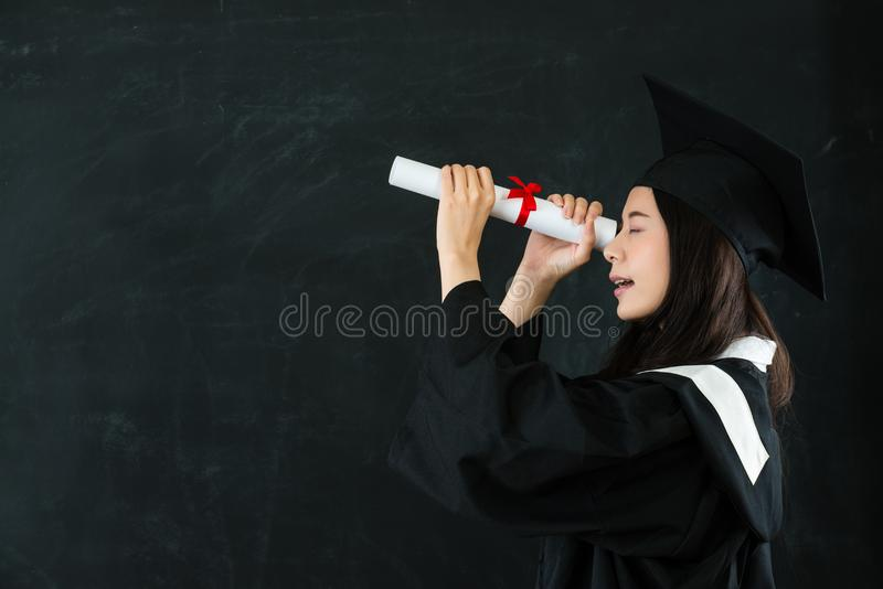 Young happy grad looking through diploma royalty free stock photo