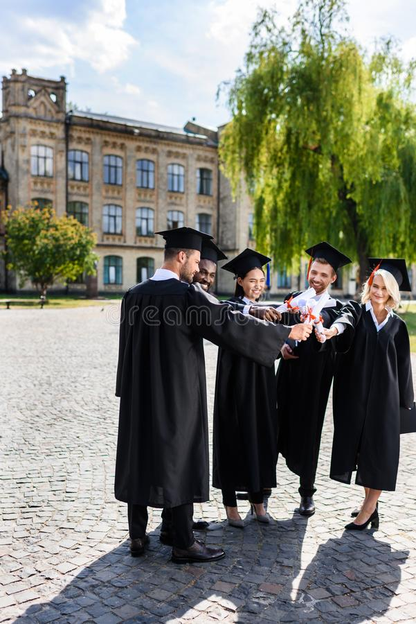 young happy graduated students making team gesture royalty free stock images