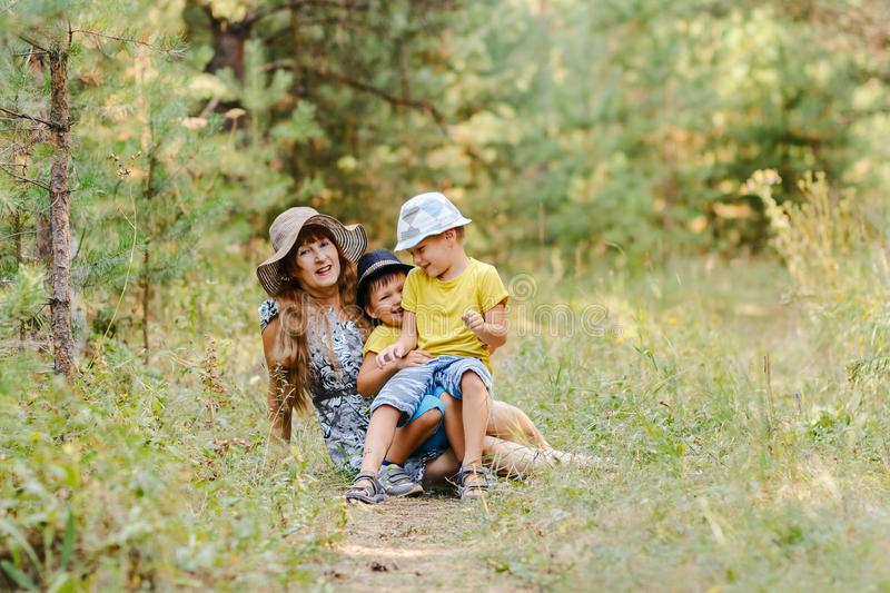 Grandmother with two grandchildren sitting on a lawn. Young happy grandmother with two grandchildren sitting on a forest lawn in the summer stock photos