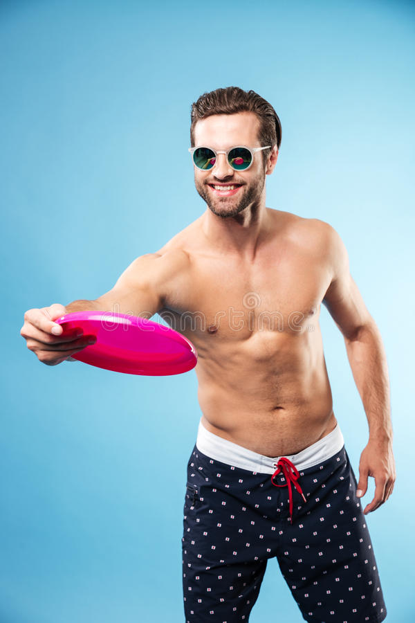 Young happy guy in summer shorts playing frisbee game stock photos