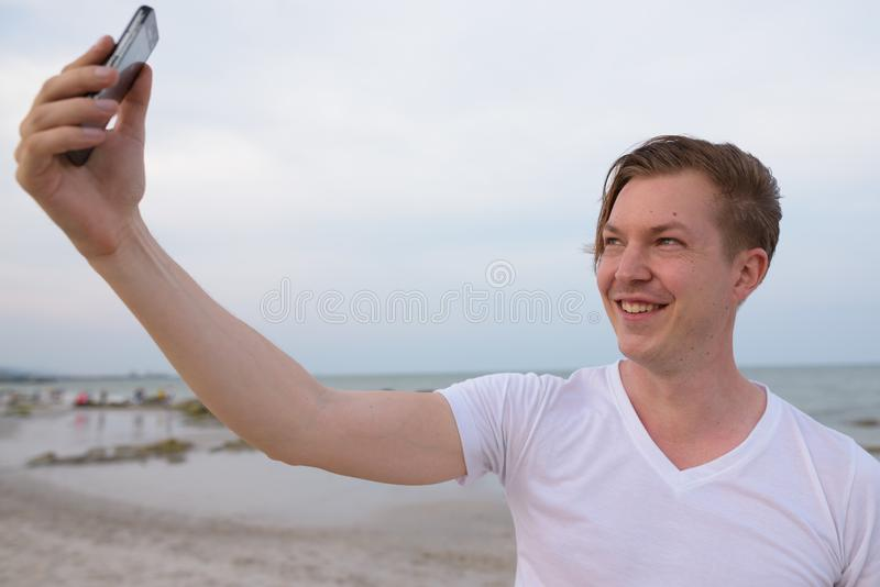 Young happy handsome man smiling while taking selfie picture wit stock photos
