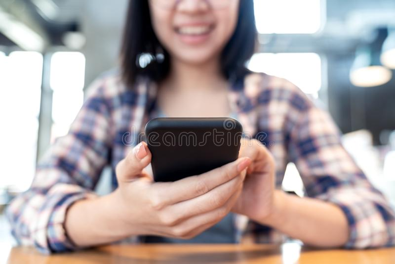 Young happy hipster asian woman using smartphone on table in cafe in social media concept. Lifestyle of millennials asian people stock image
