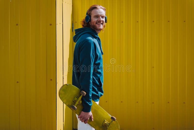 Young happy hipster man on yellow fence view stock photo