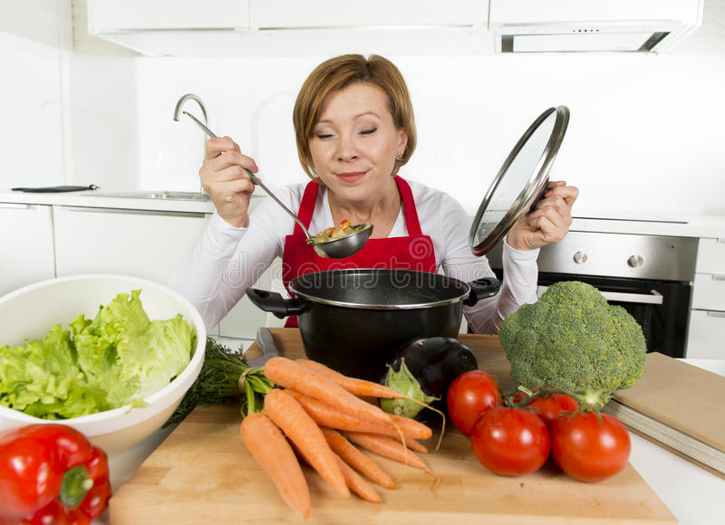 Young happy home cook woman in red apron at domestic kitchen holding saucepan tasting hot soup royalty free stock images