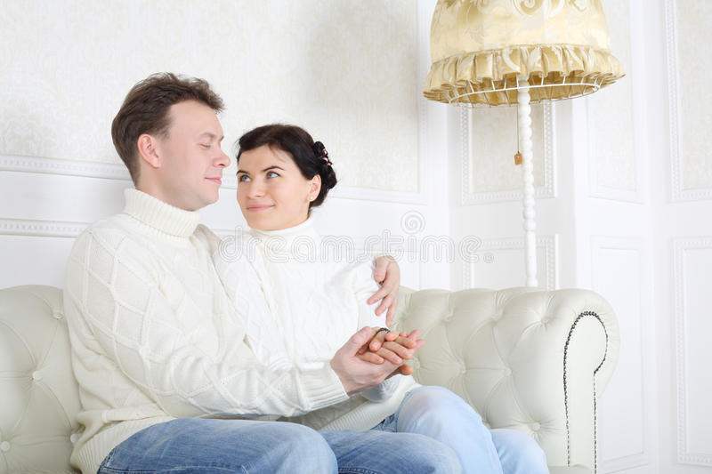 Young happy husband and wife hold hands and look at each other. On white leather sofa at home stock image