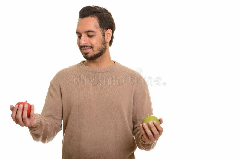 Young happy Indian man choosing between red and green apple royalty free stock photography