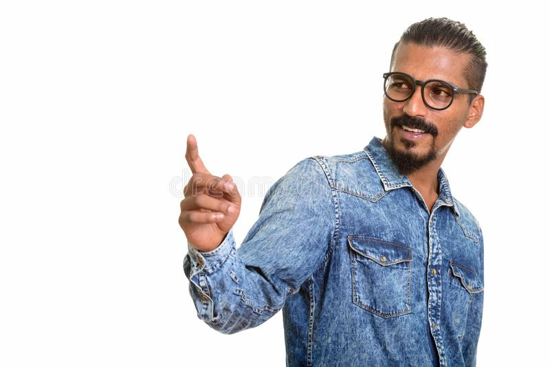 Young happy Indian man looking back and pointing finger. Isolated against white background royalty free stock photos