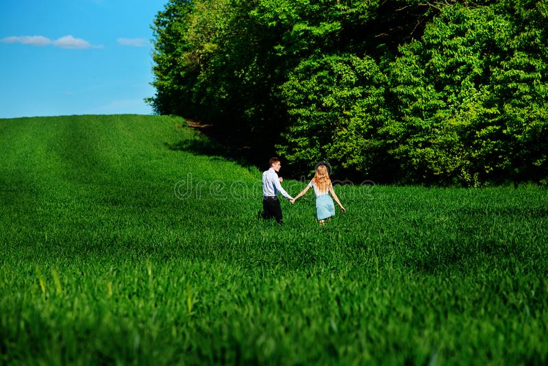 Young happy lovers running on meadow with green grass and blue s stock photography