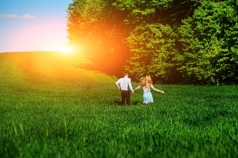 Young happy lovers running on meadow with green grass and blue s stock image