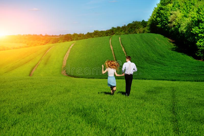 Young happy lovers running on meadow with green grass and blue s royalty free stock images