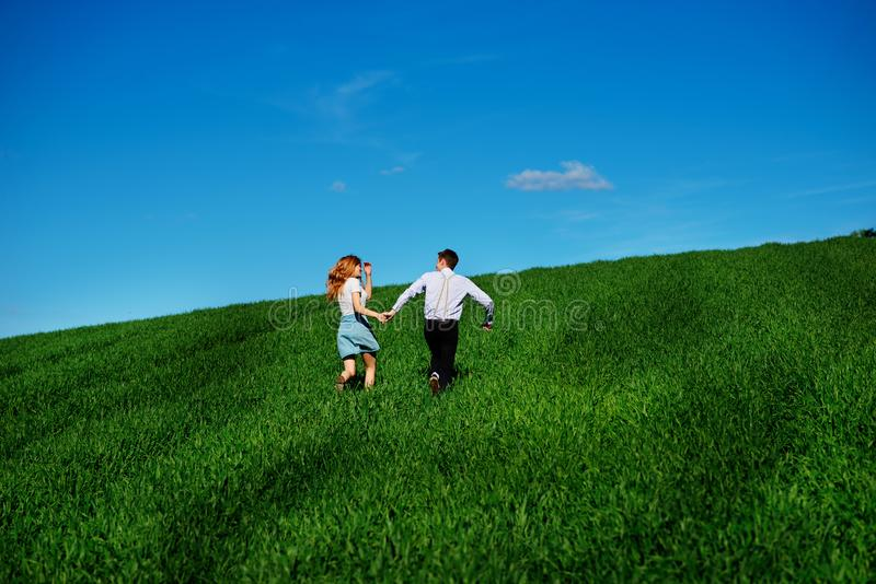 Young happy lovers running on meadow with green grass and blue s royalty free stock photos