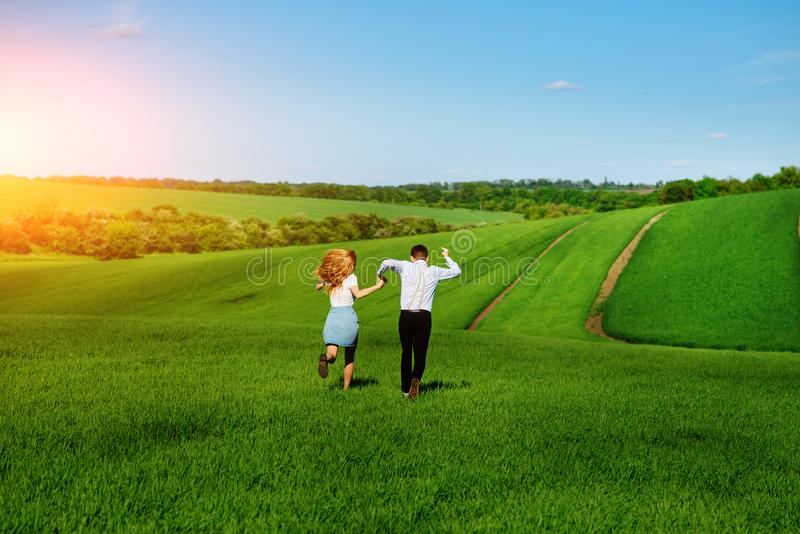 Young happy lovers running on meadow with green grass and blue s royalty free stock image
