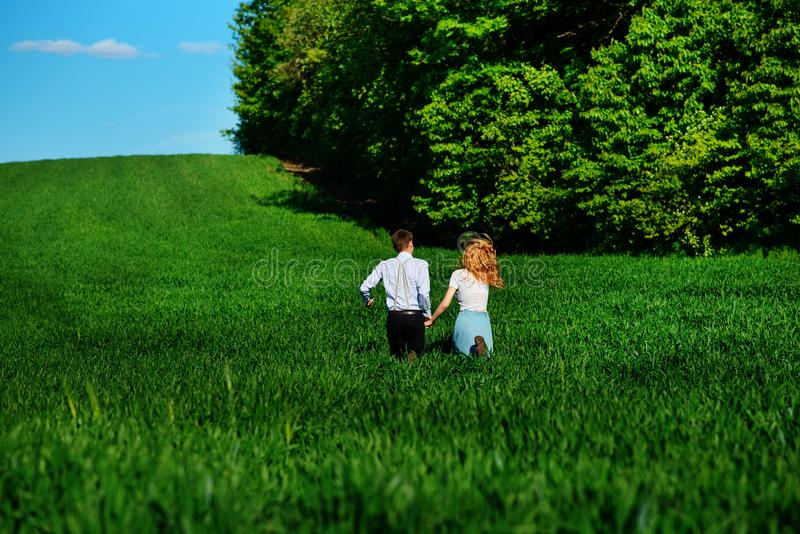 Young happy lovers running on meadow with green grass and blue s stock photo