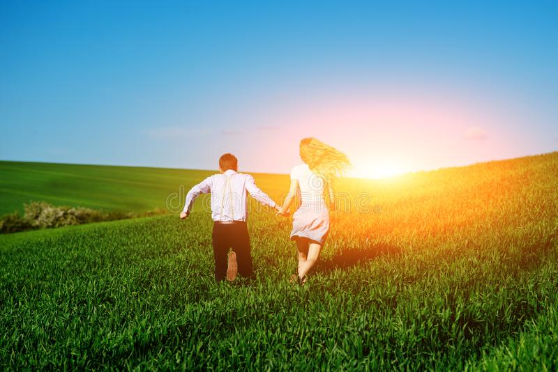 Young happy lovers running on meadow with green grass and blue s stock images