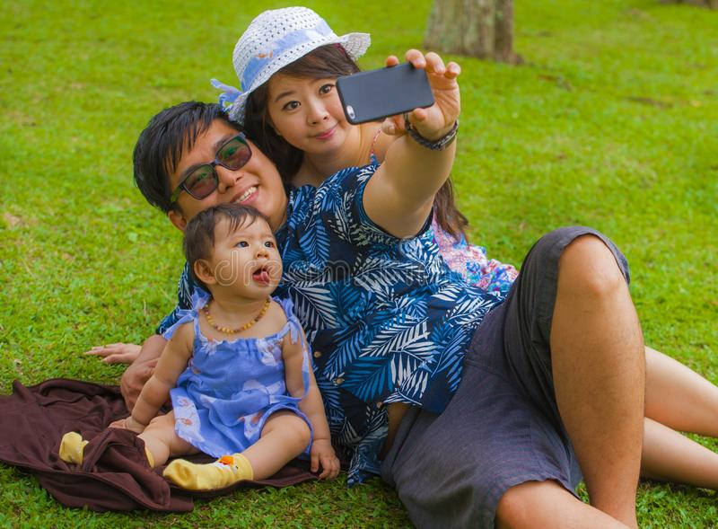 Young happy loving Asian Japanese family with parents and sweet baby daughter at city park together with father taking selfie pic stock images