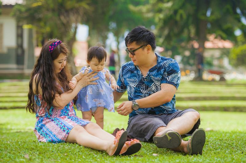 Young happy and loving Asian Japanese parents couple enjoying together with sweet daughter baby girl sitting on grass at green cit. Y park in love and beautiful stock photos