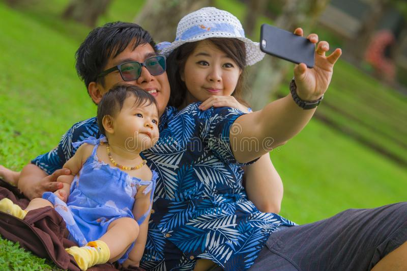 Young happy loving Asian Japanese family with parents and sweet baby daughter at city park together with father taking selfie pic royalty free stock photo