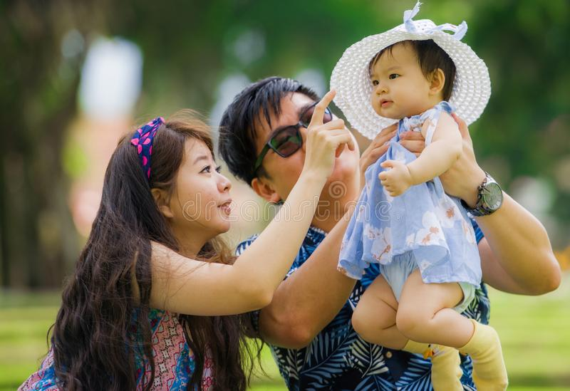 Young happy loving Asian Korean parents couple enjoying together sweet daughter baby girl sitting on grass at green city park in royalty free stock image
